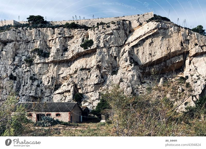 Felswand mit Haus Gestein klein Himmel Licht trocken Gestrüpp massiv feindlich grau Gesteinsschichten Außenaufnahme Farbfoto Natur Felsen Tag Berge u. Gebirge