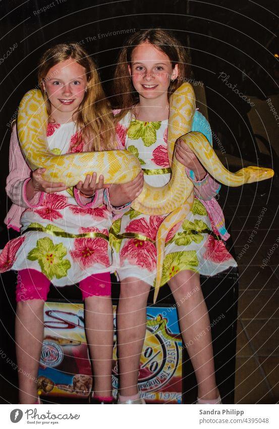 zwei Mädchen halten eine AlbinoTigerpython in den Händenund und um den Hals Schlange Zwillinge Kleider Lachen Freude Fotoshooting Fröhlichkeit Porträt