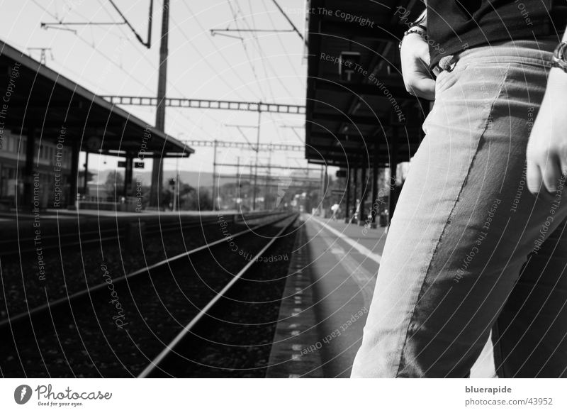 Kurz bevor Mensch Frau Hand weiß schwarz Erwachsene Beine Linie Zeit warten Uhr Eisenbahn stehen Kabel bedrohlich Jeanshose