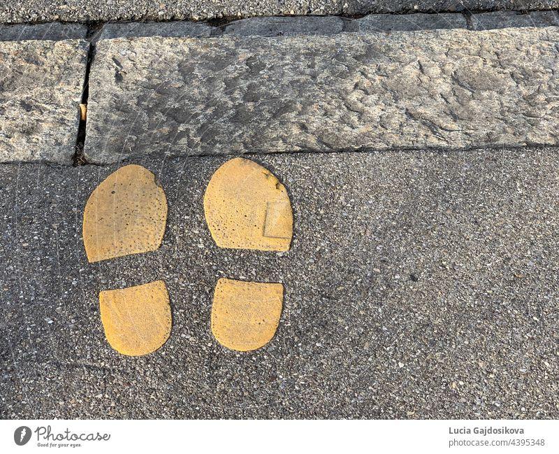 Zwei in gelber Farbe gemalte Schuhabdrücke am Rande eines Bürgersteigs. Symbol für eine Straßenkreuzung. Es ist Platz zum Kopieren vorhanden. gelbe Farbe