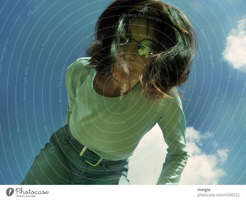 Eine Frau mit Sonnenbrille schaut nach unten in die Kamera. Über ihr ein blauer Himmel mit Wolken Junge Frau Haare & Frisuren Gesicht Porträt feminin Mensch