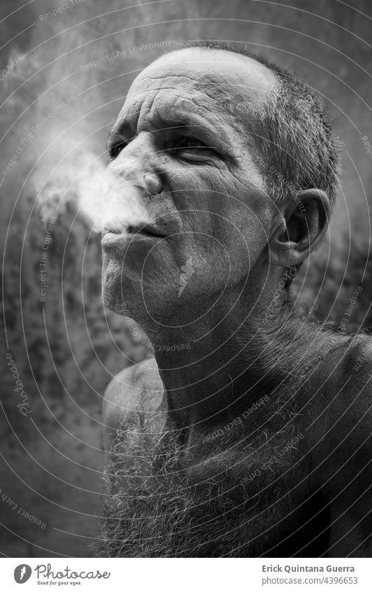 Alter Mann raucht Zigaretten schwarz auf weiß Porträt alter Mann Rauch tabacco Nikotin ungesund Sucht Zigarettenabhängigkeit gesundheitsschädlich