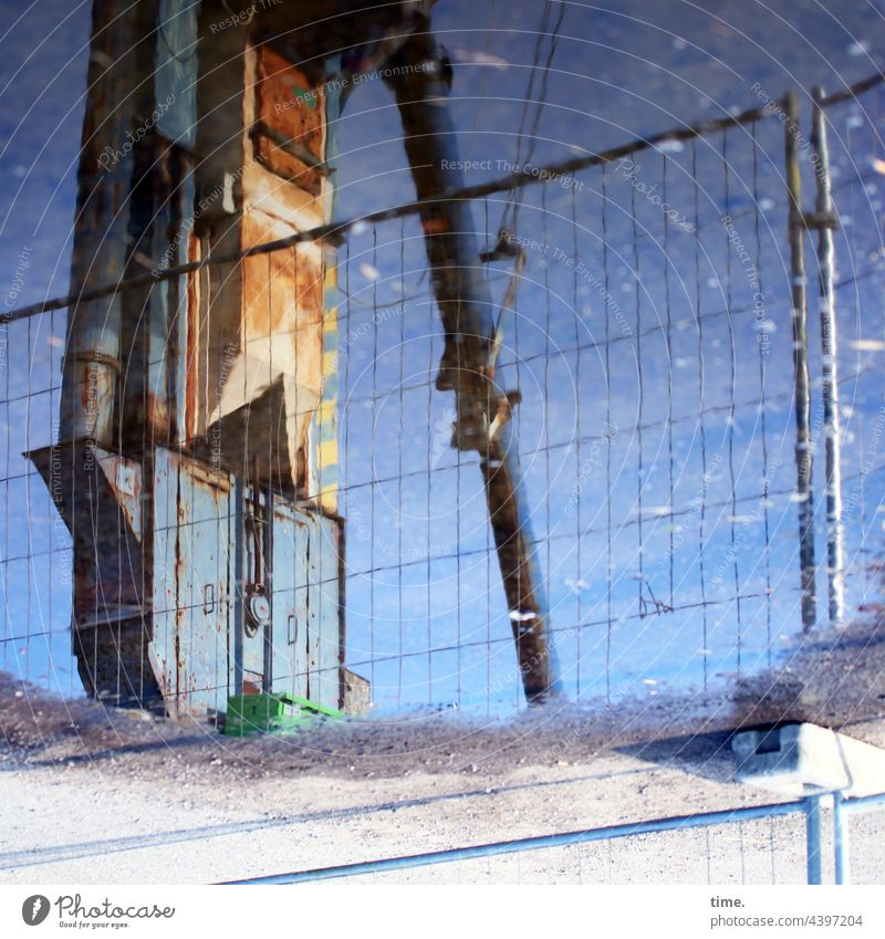 Geschichten vom Zaun (108) bauzaun sonnig kran beton sand reflexion spiegelung alt trashig rohr kette gewicht Zaunanker pfütze nass metall bauwerk