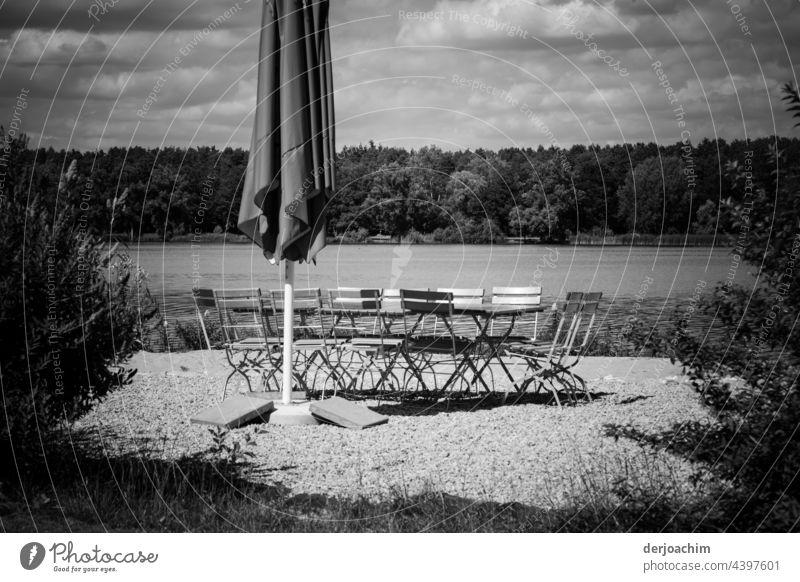 Ein eingeklappter Sonnenschirm,  ein paar leere Stühle und Tisch , sowie das Wasser von einem See und im Hintergrund ganz viel Wald. Zu allem am Himmel viele Wolken. Jetzt fehlen nur noch die Gäste...