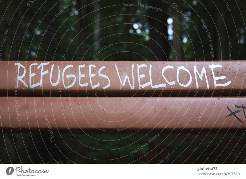 Refugees welcome - Flüchtlinge willkommen | Schriftzug auf einer Bank Graffiti Außenaufnahme Park Schriftzeichen Menschenleer Humanität menschlich Willkommen