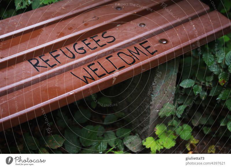Refugees welcome - Flüchtlinge willkommen | Schriftzug auf einer Bank Graffiti Willkommen Park Außenaufnahme Schriftzeichen Menschenleer Farbfoto