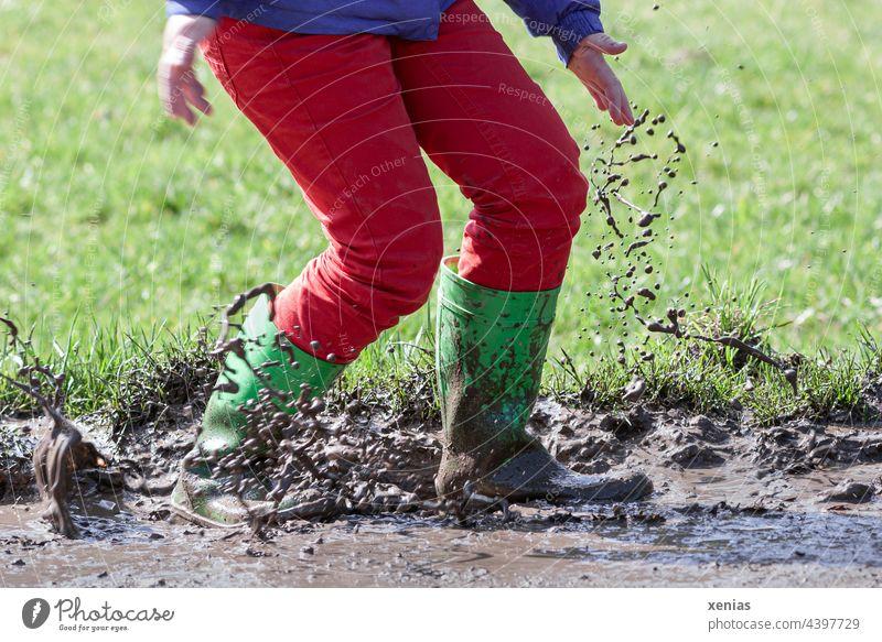 Mit grünen Gummistiefel und roter Hose in den Matsch springen macht Spaß spritzen dreckig kleckern Freude Pfütze Spielen Herbst Schlamm braun Kindheit Jeanshose