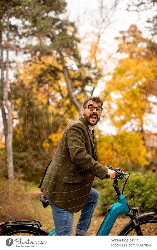Junger Mann mit Elektrofahrrad im herbstlichen Park Fahrrad jung Natur elektrisch Lifestyle im Freien Aktivität Farbe Zyklus Mitfahrgelegenheit Sommer Tag
