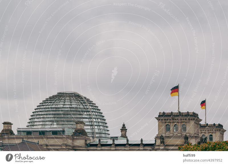 Deutschlandfahne auf dem Reichstag in Berlin bei aufkommendem Unwetter - stürmische Zeiten schwarz-rot-gold Fahne wehen Politik & Staat Wahrzeichen Falte gelb