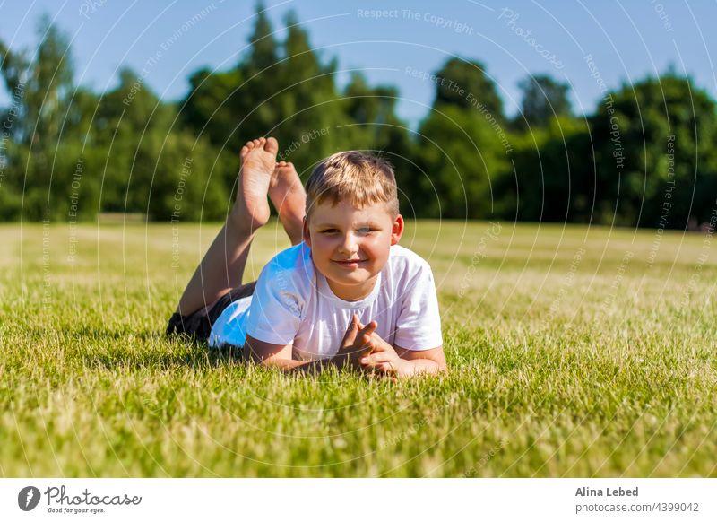Ein fröhliches Kind lächelt vor Freude. Ich bin glücklich zu gehen und spielen auf dem Rasen in warmen sonnigen Wetter im Park. die Emotionen der Kinder auf dem Gesicht.