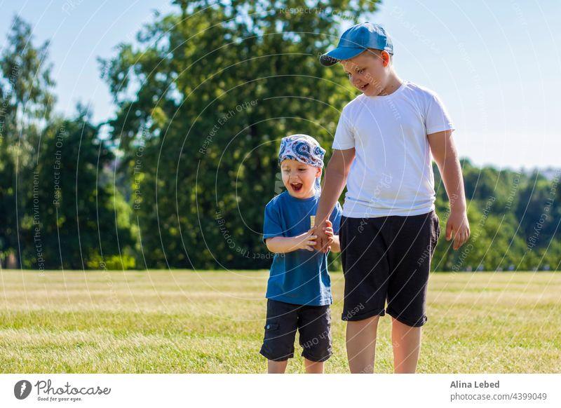Fröhliche Kinder, zwei Brüder, lächeln vor Freude. Wir sind glücklich zu gehen und spielen auf dem Rasen in warmen sonnigen Wetter im Park. die Emotionen der Kinder auf dem Gesicht.