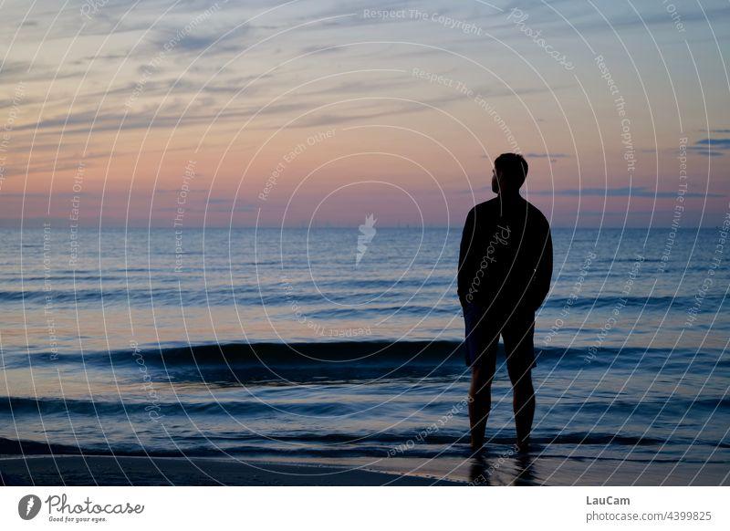 Die Sonne ist gerade untergegangen. In der Abendstimmung steht ein Mann am Strand im Wasser und blickt in die Ferne... Sonnenuntergang Dämmerung