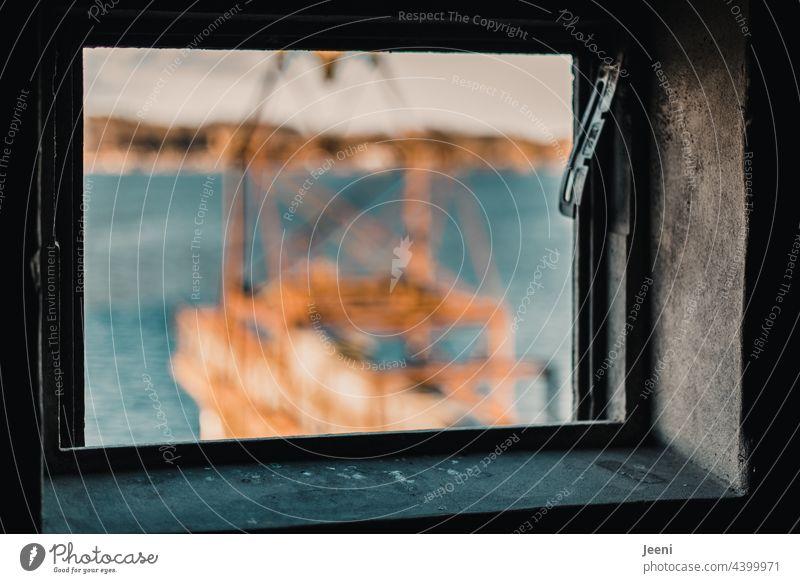 Verschwommener Ausblick aus dem kaputten Fenster des alten Hafenspeichers auf die verrostete und in die Jahre gekommene Krananlage Blick ausblick fensterlos
