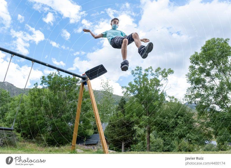 Ein junger Mann, der eine Hygienemaske trägt, springt von einer Schaukel auf einem Spielplatz in das leere Wasser. springend pendeln fliegen Gesichtsmaske