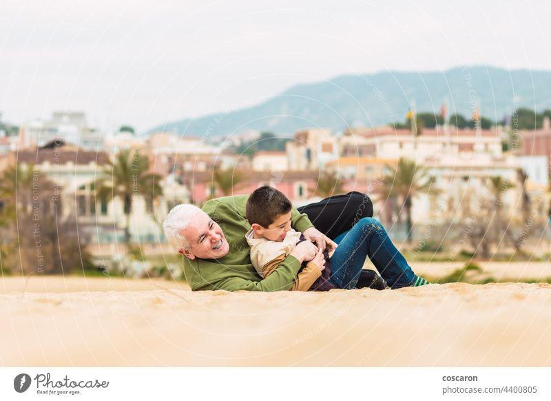 Lustiger Junge und sein Großvater spielen ausgestreckt im Sand am Strand aktiv Kaukasier Kind Kindheit niedlich el masnou Familie Spaß Generation Generationen