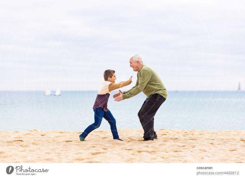 Fröhlicher Junge, der seinen Großvater am Strand umarmen will sorgenfrei heiter Kind Kindheit Kinder Papa älter Familie Vater Gefühl Spaß Generation Enkel