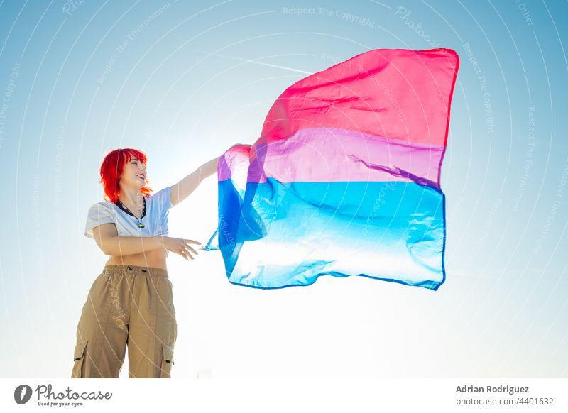 Frau hält die bisexuelle Regenbogenflagge mit dem blauen Himmel im Hintergrund Fahne lgbt Homosexualität Stolz lesbisch Rechte lgbtq Liebe schwul Symbol