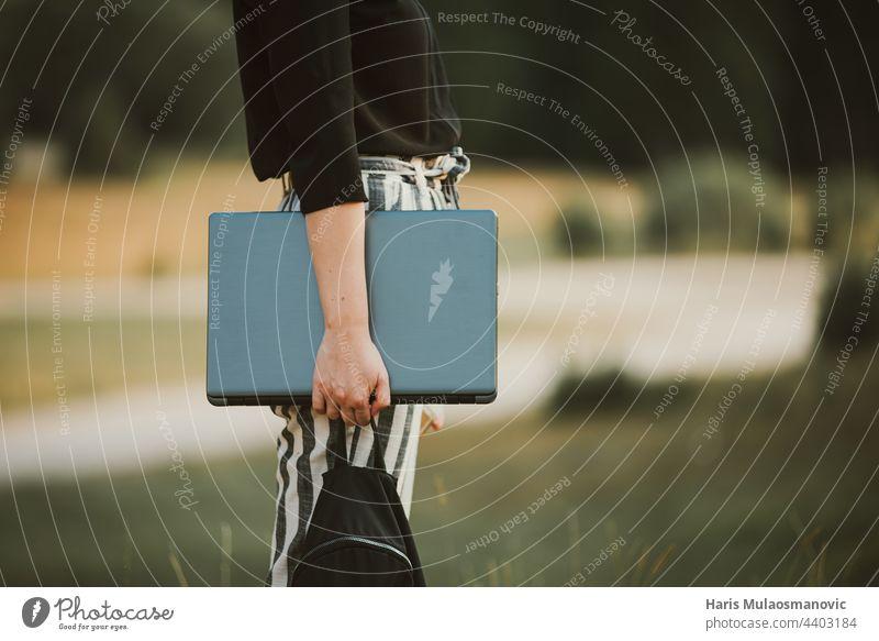 Frau Freiberufler hält Laptop im Freien in der Natur 5g Konzept Anschluss Entwickler digital digitaler Nomade Gerät erkunden Freiheit freiberufliches Konzept