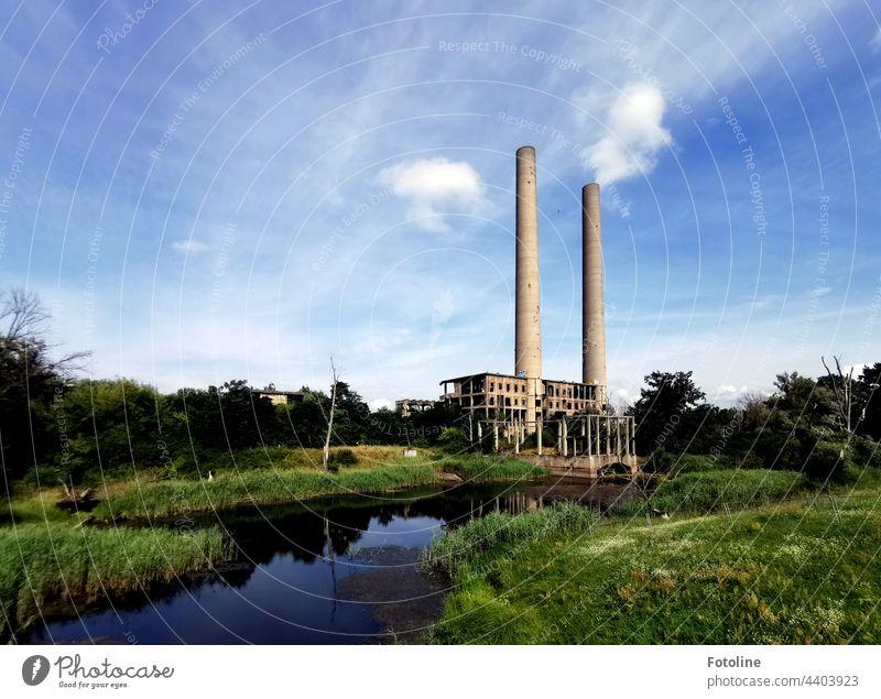 Lost Place - ein altes Kraftwerk an der Oder, das zwar gebaut, aber nie in Betrieb genommen wurde. 2 Schornsteine ragen in den blauen, leicht bewölkten Himmel.