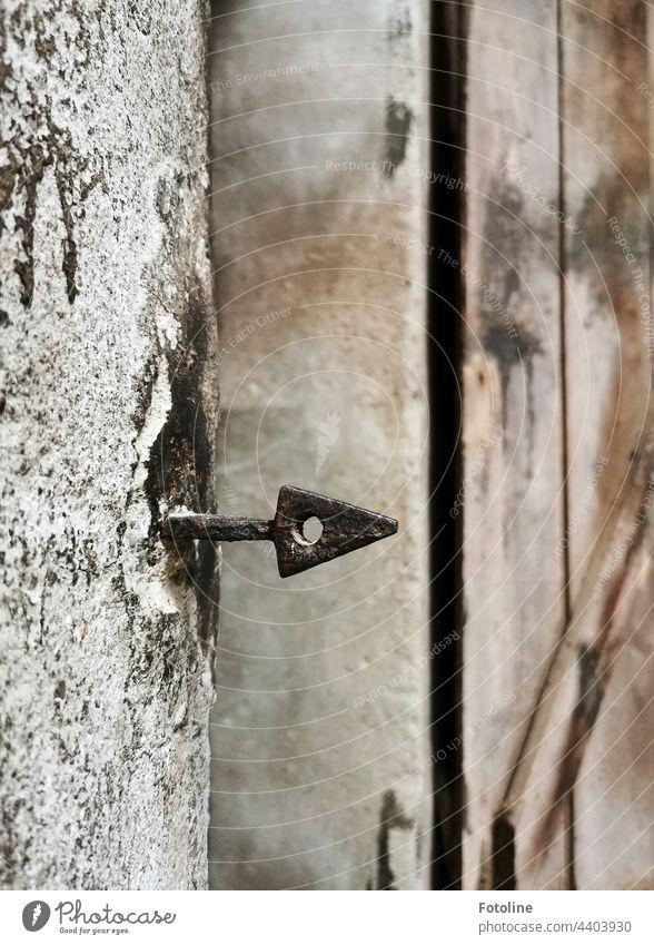Lost Place - aus einer alten Wand ragt ein schmiedeeiserner Pfeil. Mauer Menschenleer Spitze Loch dreieckig rund richtungsweisend Schwache Tiefenschärfe grau