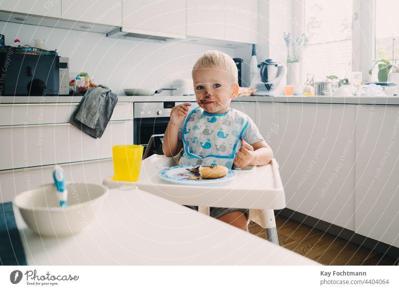 Entzückendes Kleinkind mit schokoladenverschmiertem Gesicht 12-23 Monate Sucht bezaubernd Baby blondes Haar blaue Augen Bonbon Kaukasier kaukasische Ethnizität