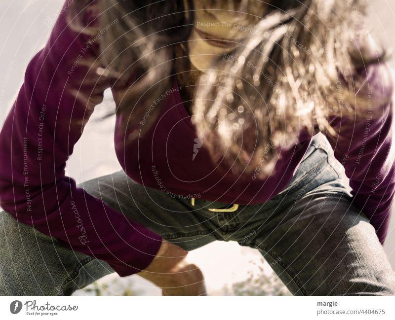 Eine Frau sitzt in der Hocke und schaut in die Kamera (Ausschnitt) Porträt Gesicht Mensch Haare & Frisuren lange Haare Jeanshose ausschnitt ausschnitt portrait