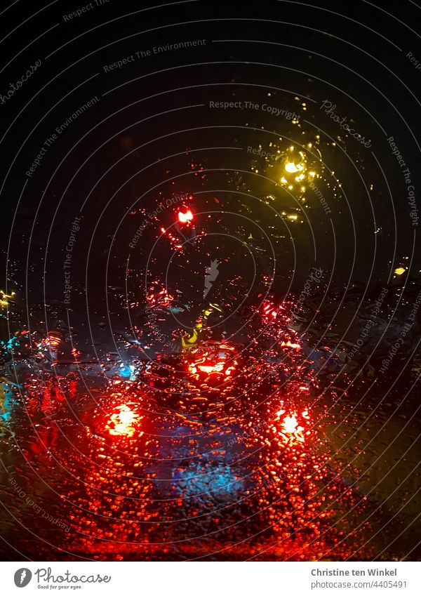 Blick durch die regennasse Windschutzscheibe auf beleuchtete Autos, die in der Dunkelheit an einer Ampel warten Regen Lichter im Regen Autolichter verregnet