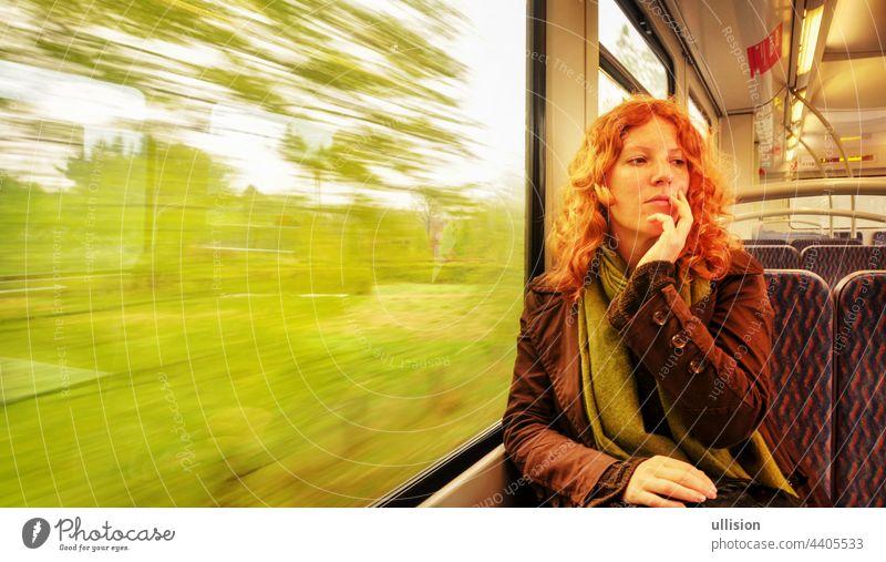 Junge rothaarige schöne sexy Frau sitzt tagträumend tagträumend in einem fahrenden Nahverkehrszug mit Kopierraum Textfreiraum Tagträumen Sitzen Vorortzug U-Bahn