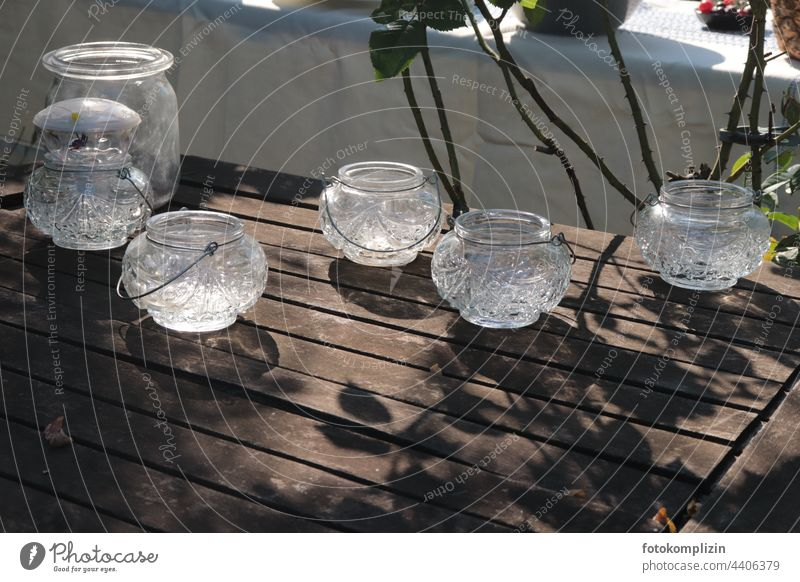 Kerzenlicht-Gläser auf einem Gartentisch Tischdekoration Kerzenglas Teelicht Gartenfest Teelichtständer Teelichter gläsern Holztisch festlich
