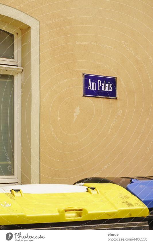 lila Straßennamenschild - Am Palais - an einer beigefarbenen Hauswand und zwei Müllcontainer vor dem Fenster / wohnen Straßenschild