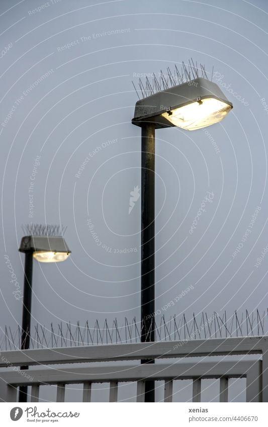 Vögel unerwünscht - Zwei leuchtende Laternen mit Stachel vor Gitter und grauem Himmel bei Dämmerung Lampe Straßenbeleuchtung Vogelabwehr Licht Pickser zwei