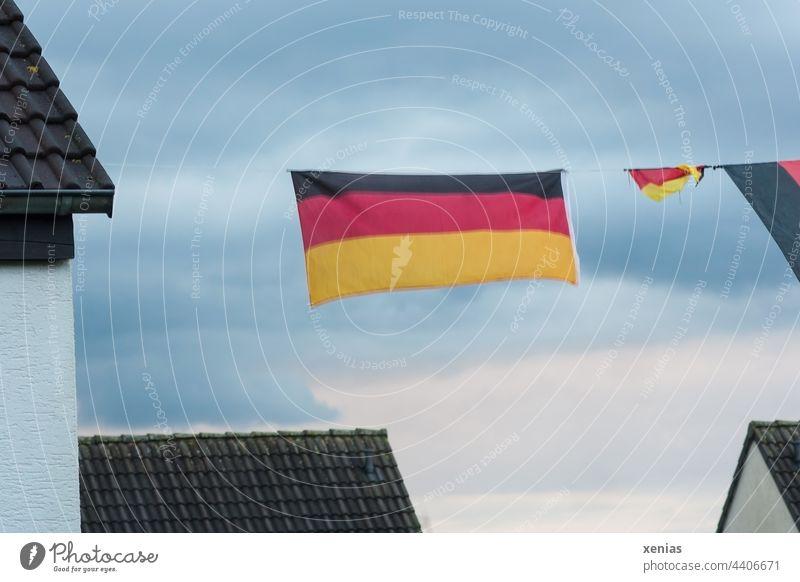Eine Deutschlandfahne und ein Deutschlandfähnchen hängen auf der Leine zwischen Häusern unter bewölktem Himmel Fahne Flagge schwarz rot gold Wolken Nation