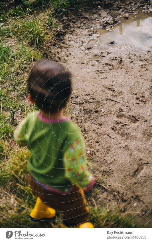 Junge mit Gummistiefeln steht vor einer Schlammpfütze Jungen sorgenfrei kaukasische Ethnizität Kind Kindheit niedlich Tag Genuss Spaß Fröhlichkeit horizontal