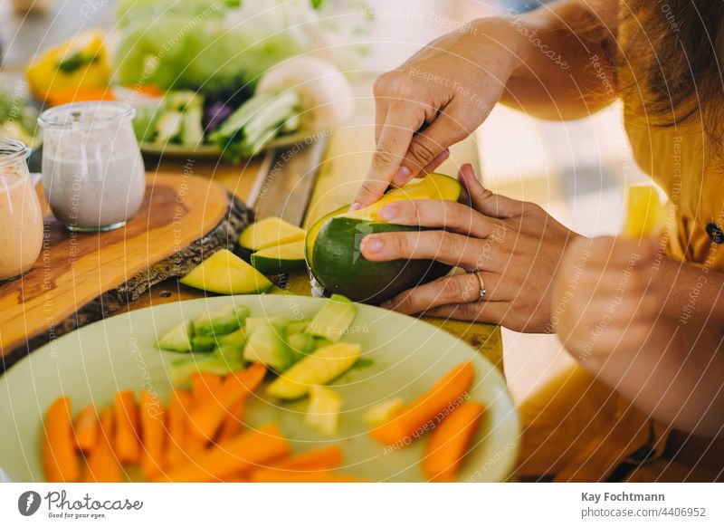 Foto einer Frau, die eine Mango zubereitet Amuse-Gueule Möhre Nahaufnahme geschnitten Schneiden lecker Diät Abendessen Speise exotisch Lebensmittel
