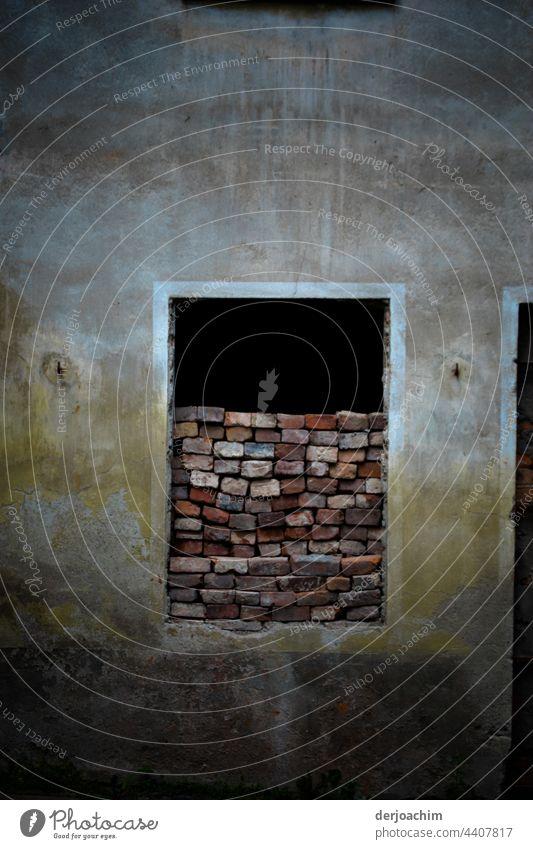 Das Haus ist verlassen. Die Tür fehlt. Dafür wurde mit bunten Backsteinen eine halbhohe Mauer aufgerichtet. Farbfoto Fassade Architektur Fenster Stadt trist Tag