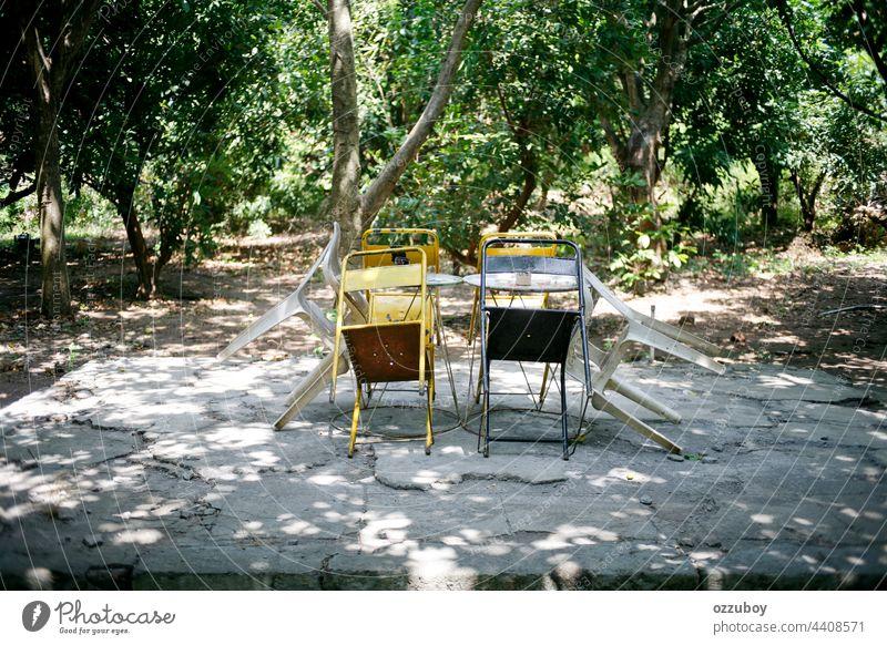 leere Stühle und Tische im Park Stuhl Holz Garten im Freien hölzern Möbel Bank Natur niemand Hintergrund Sommer außerhalb ruhen Sitz Farbe grün Baum Rasen Szene
