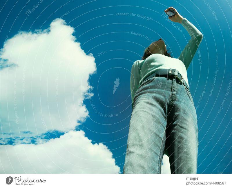 Himmel, Wolken, eine Frau sucht die Verbindung in ihrem Smartphone, Handy Blauer Himmel Sonne Schönes Wetter handyfoto Sonnenlicht Jeanshose jeans Gürtel