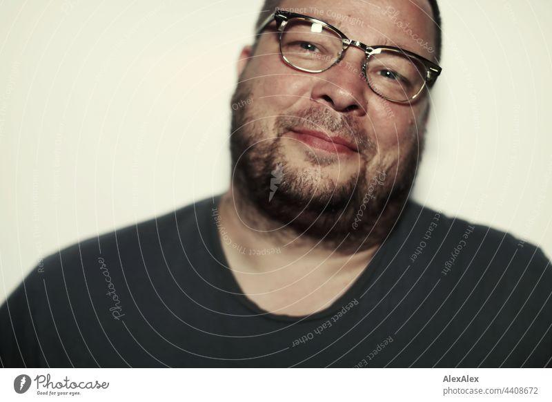 Nahaufnahme eines lächelnden Mannes mit Brille und 3-Tage-Bart schlicht ausnehmen Porträt sportlich gutaussehend seriös Fotograf im Inneren maskulin gerade