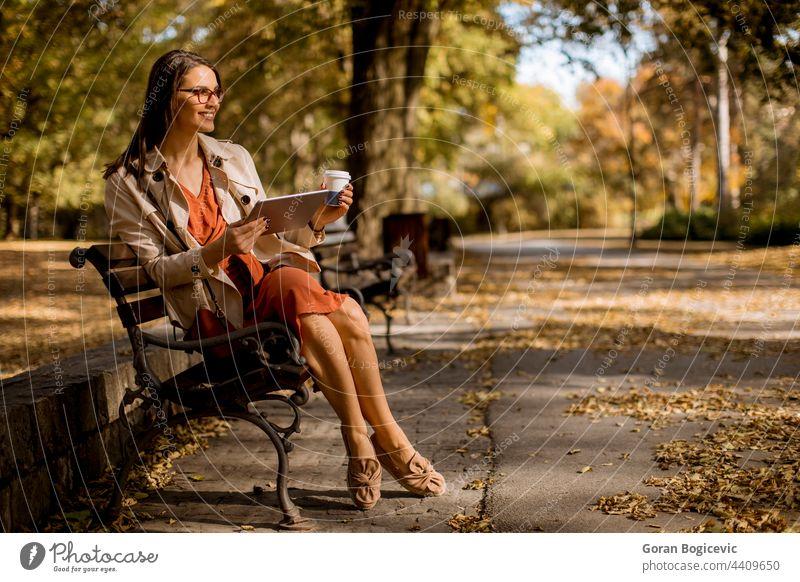Junge Frau trinkt Kaffee und benutzt ein digitales Tablet im Park allein attraktiv Herbst Bank Kaukasier Gerät Wald Internet Laptop Blätter Freizeit Lifestyle