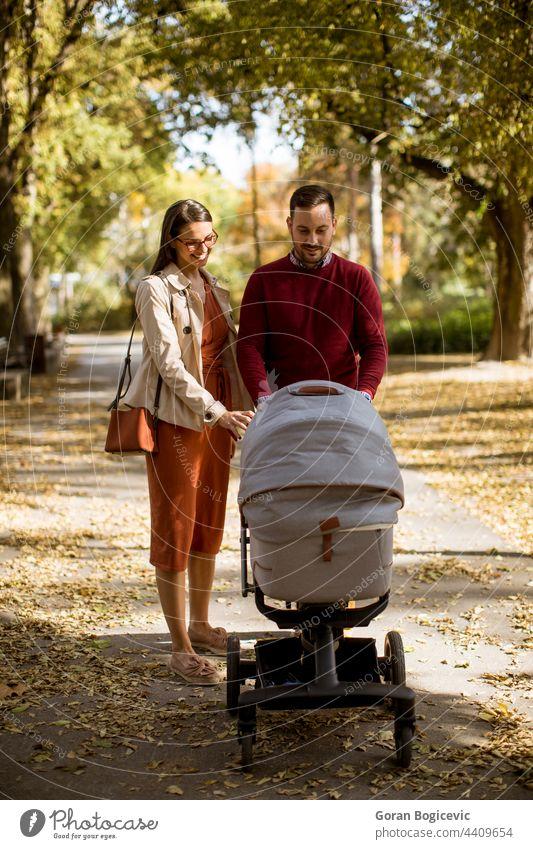 Glückliche junge Eltern, die im Park spazieren gehen und ein Baby im Kinderwagen fahren bezaubernd Herbst Wagen Kindheit Papa Familie Vater Freizeit Lifestyle