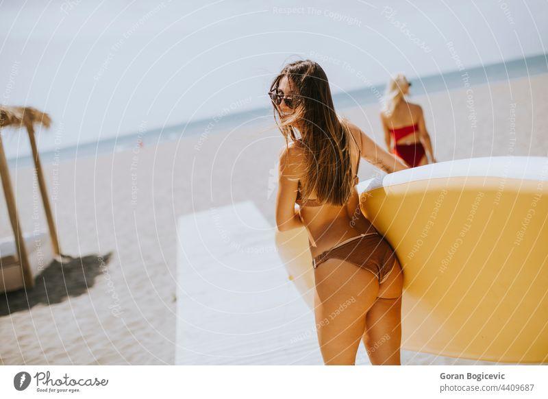 Zwei junge Frauen mit Paddelbrett am Strand an einem Sommertag attraktiv schön Bikini Holzplatte Küste Tag passen Freunde Freundschaft Spaß Glück Lifestyle Meer