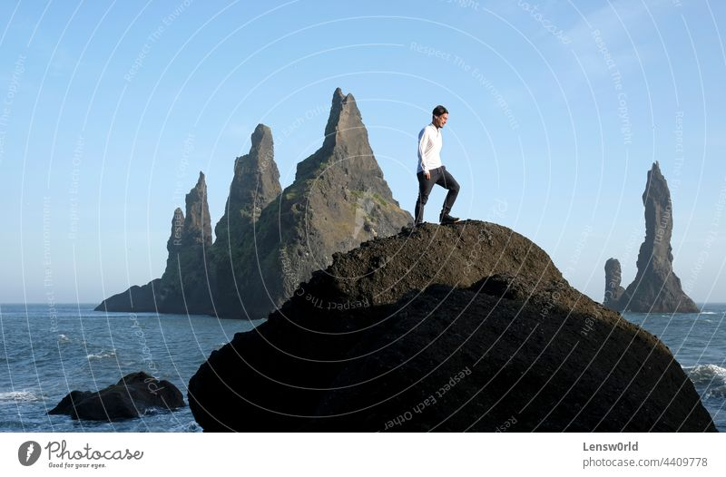 Mann steht auf einem Felsen am Reynisfjara Black Beach, Island, mit Wind in den Haaren Abenteuer schwarzer Strand blau Klippe Konzept Freiheit gutaussehend