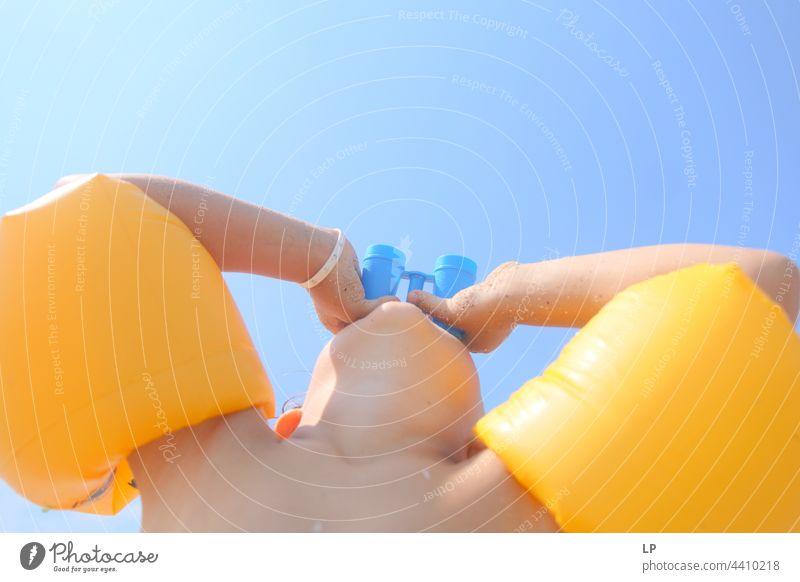 Kind schaut durch ein Spielzeugfernglas im Freien Wegsehen beobachten positiv Ufer Freiheit Urlaub Fernglas Seeküste genießend sorgenfrei Kindheit lässig