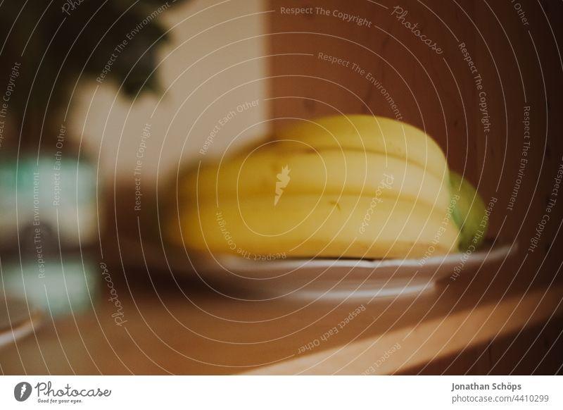drei Bananen auf einem Teller im Regal in der Küche Obst Südfrucht Südfrüchte süß Fruktose Fructose gelb gesund zuhause drinnen Aufbewahrung Unschärfe