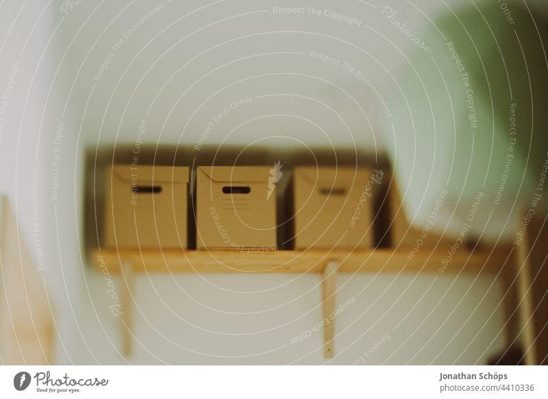 Pappkisten auf dem Regal oben an der Wand im Flur aus Recycling Pappe Innenaufnahme Schachtel Menschenleer Wellpappe drinnen Verpackung Pappkarton Karton Kiste