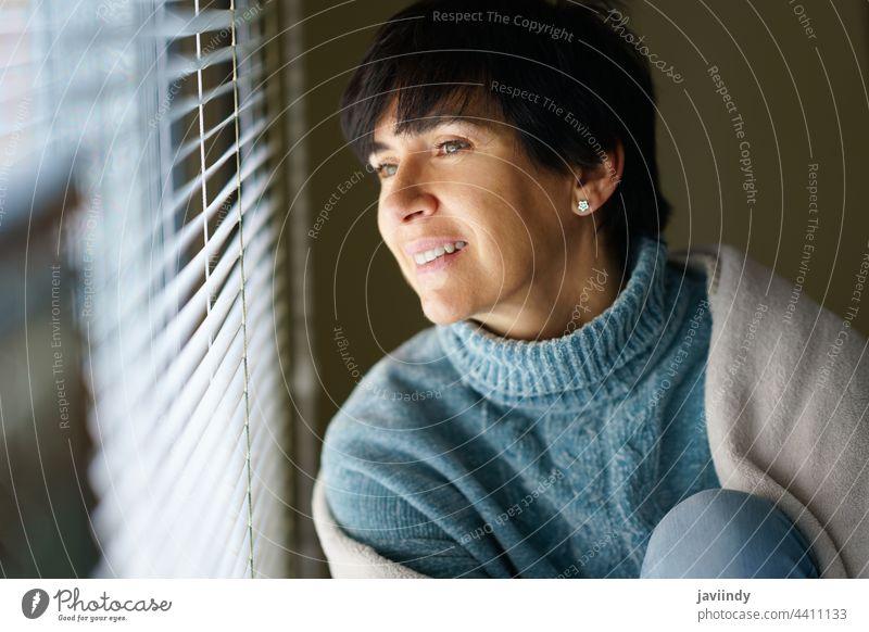 Glückliche Frau mittleren Alters, die lächelnd aus dem Fenster schaut. Lächeln heimwärts 50s 40s Person brünett Menschen Innenbereich sich[Akk] entspannen weiß