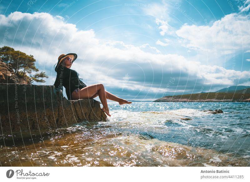 Erstaunlich Blick auf eine Brünette sitzt auf einem Felsen in der Nähe des Meeres. Erstaunliche Sommerwetter in Kroatien, vis Insel. Sonnenbaden in der Sonne mit Wellen, die an das Ufer schlagen