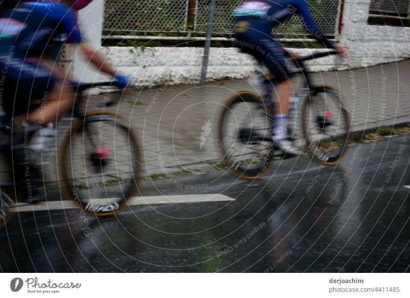 Zwei Radrennfahrer treten voll in die Pedale, kurz bevor sie  einen Anstieg  erreichen . Sie sind beide unscharf. radfahrer Fahrrad Fahrradfahren Straße