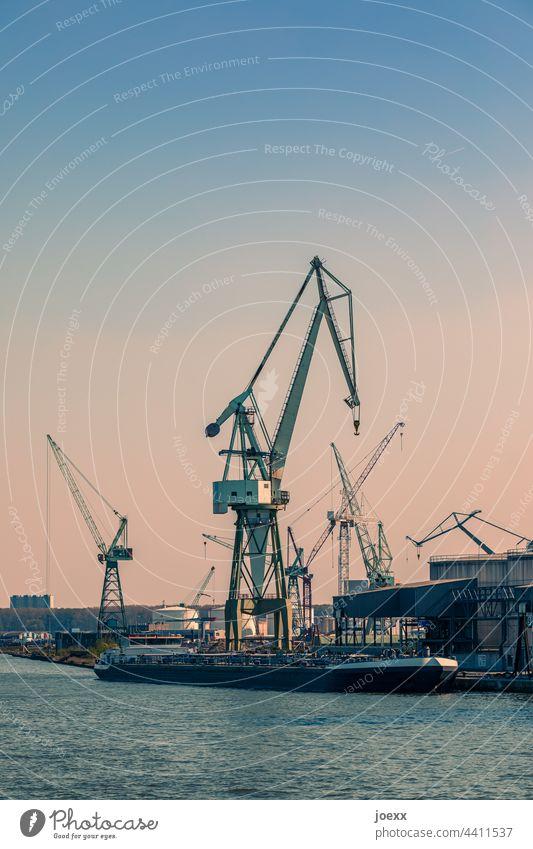 Lastenkräne in Industriehafen am Wasser mit angelegtem Schiff Kran Hafen Kräne Binnenschifffahrt Industrieanlage Flussufer Schönes Wetter Himmel alt