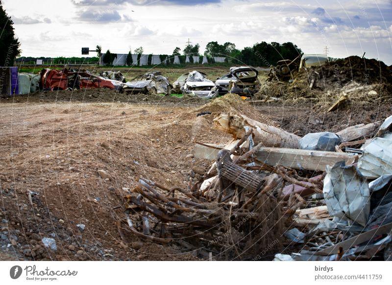 Nach der Flutkatastrophe in Erftstadt - Blessem , zerstörte Autos und Bauschutt am Ufer der Erft.Im Hintergrund die unterspülte A 61 mit abgestürzten Lärmschutzwänden